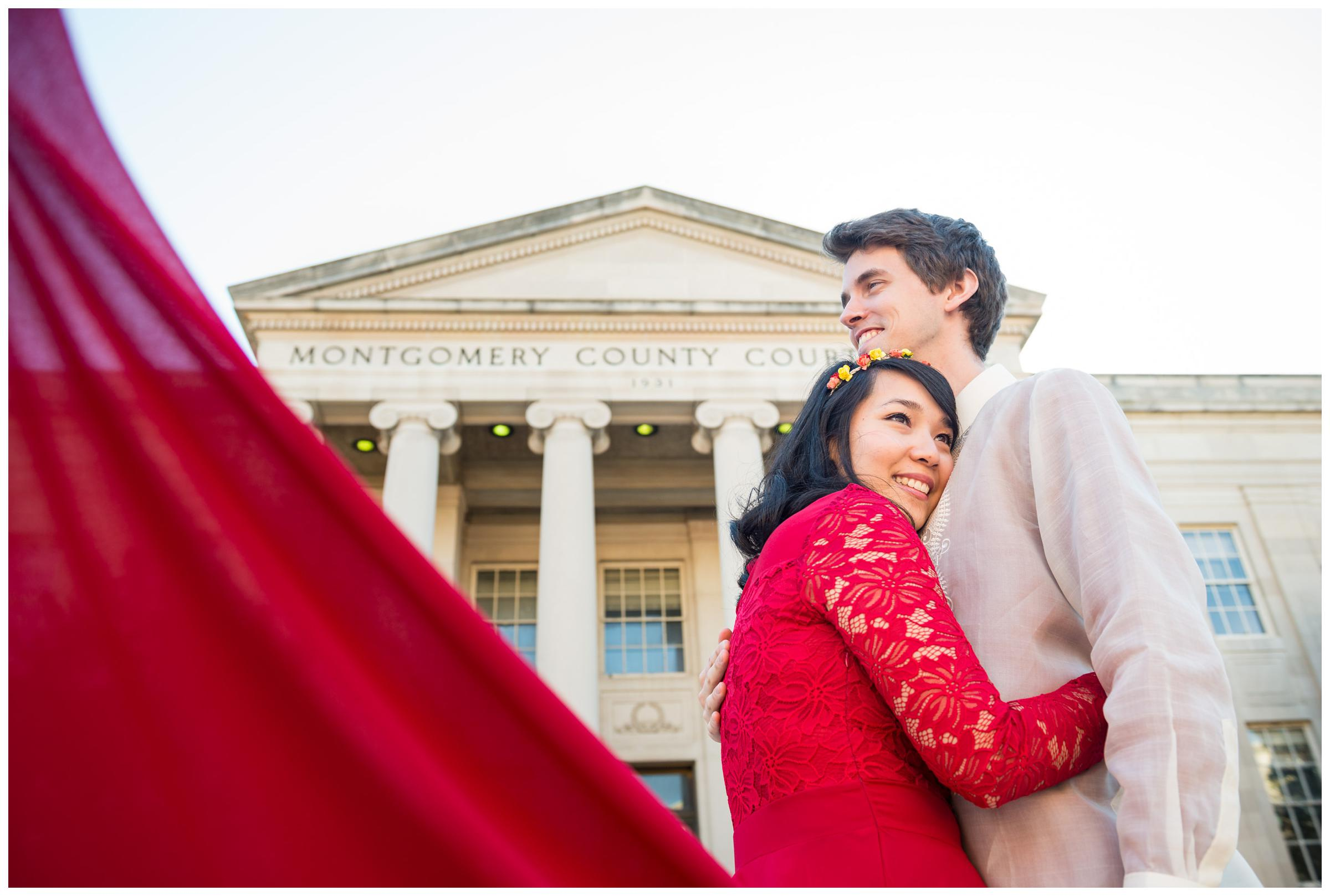 groom with bride in red wedding dress outside of courthouse in Rockville, Maryland