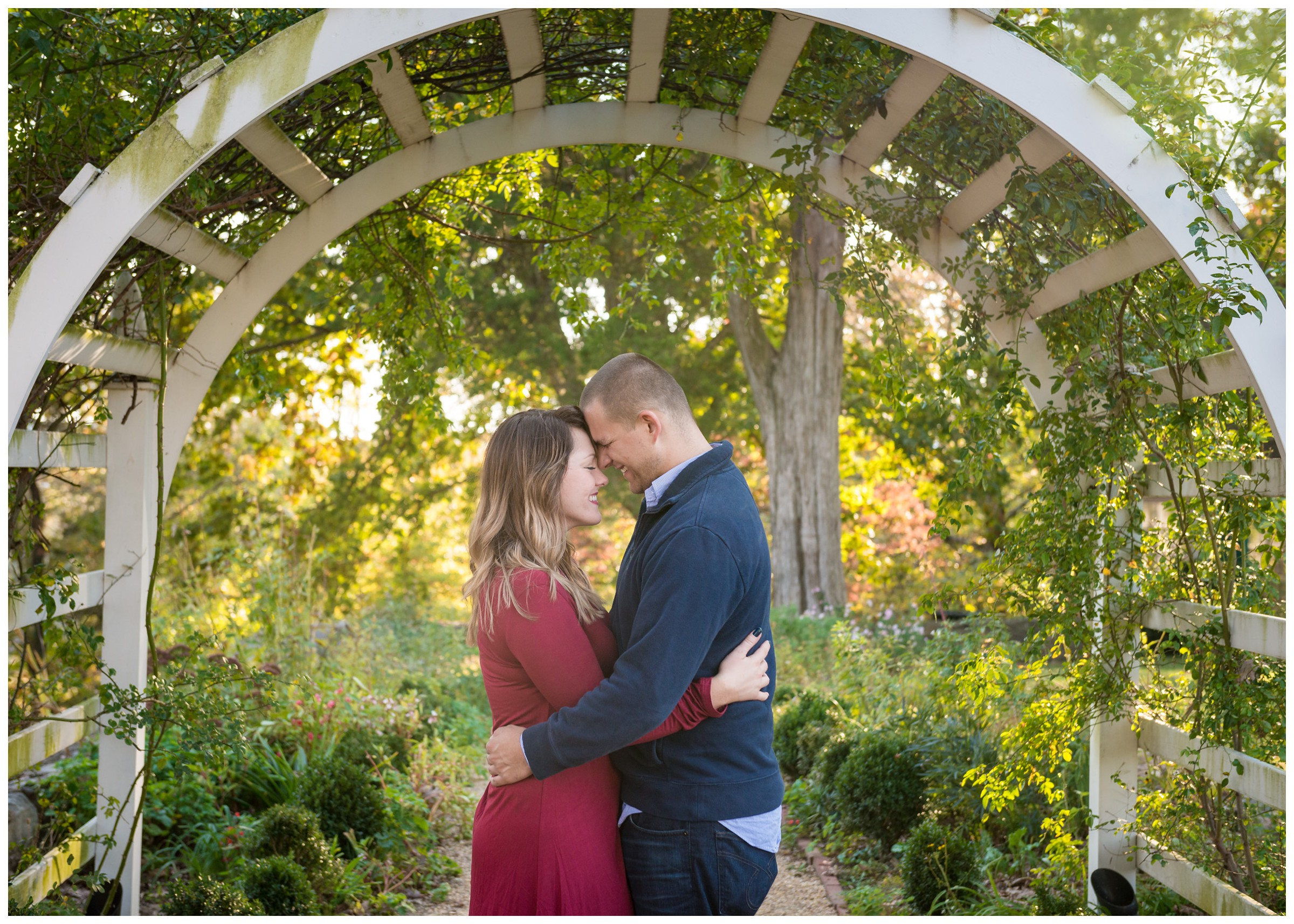 engaged couple under archway with fall foliage at Belmont in Fredericksburg, Virginia