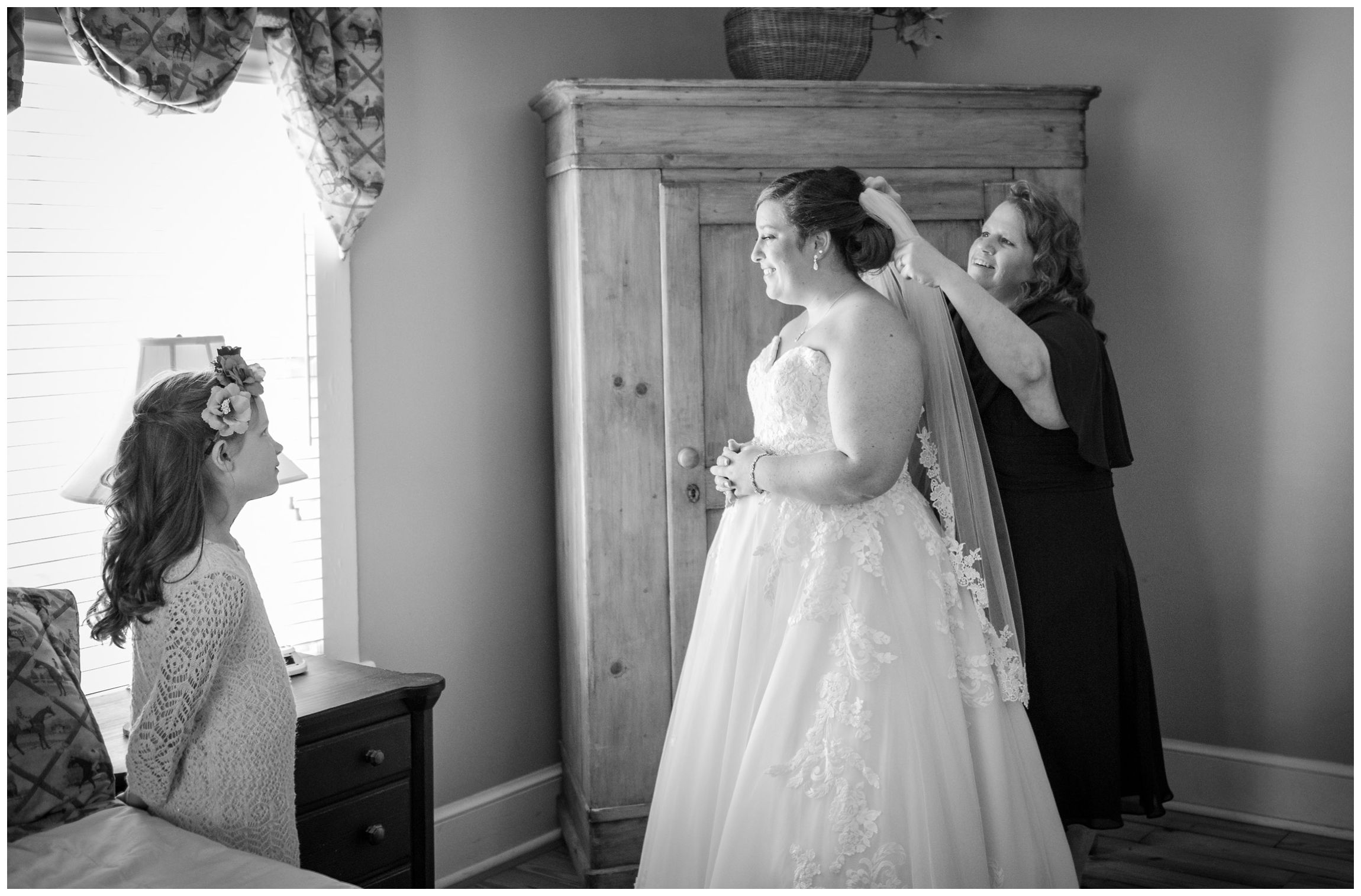 bride's mom putting on her veil while flower girl watches