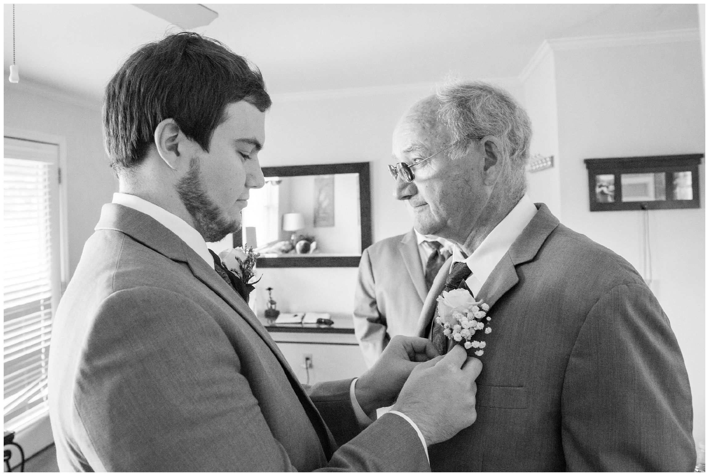 groom pins boutonniere on his dad and best man