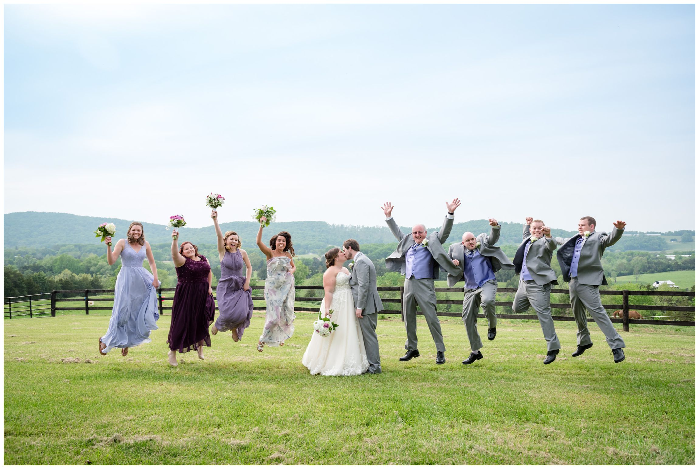 bridal party jumping against mountain backdrop after wedding at Wolftrap Farm in Virginia