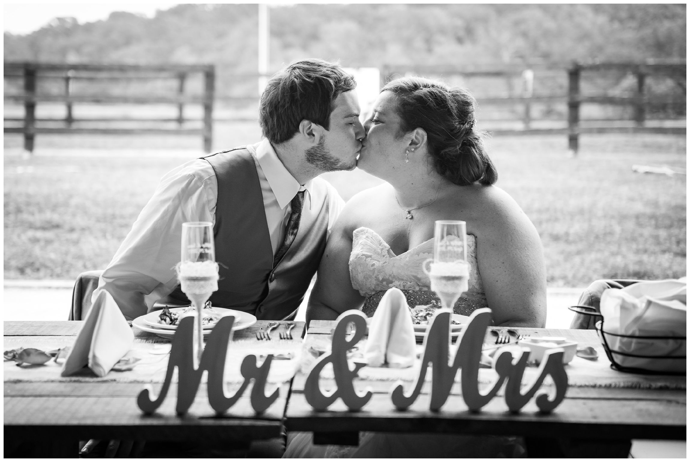 bride and groom kissing at head table during barn reception