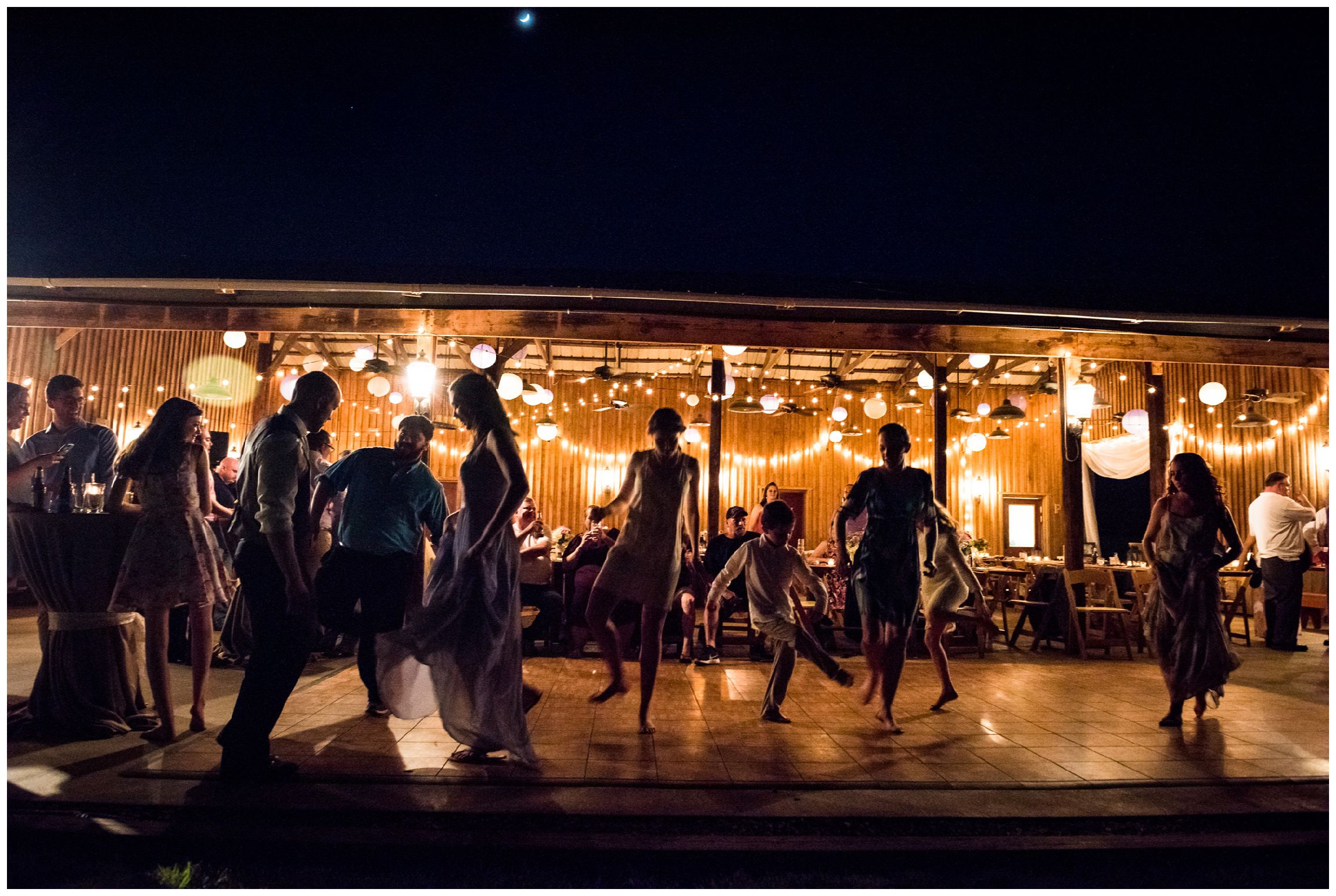 silhouettes of guests dancing at nighttime barn wedding reception