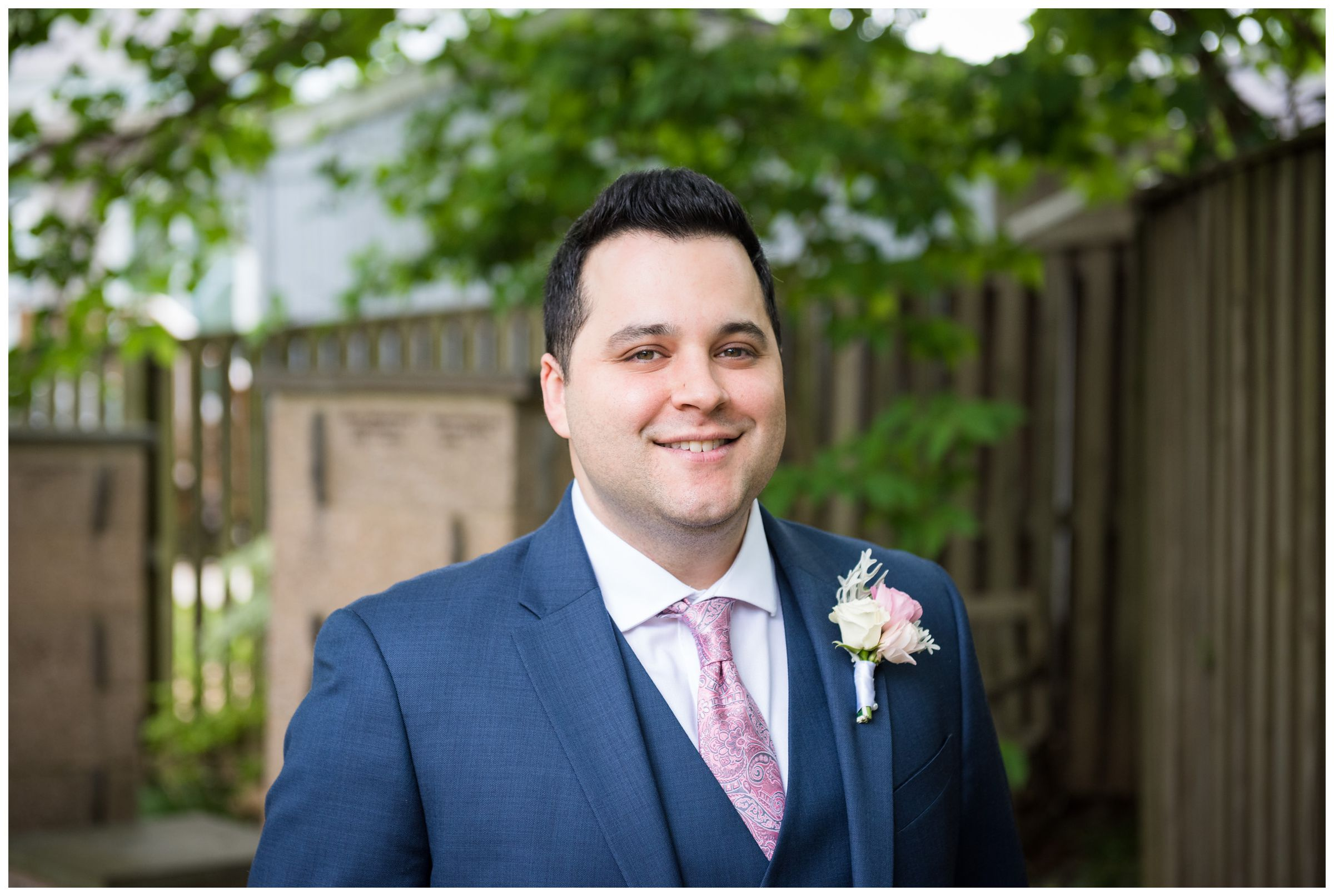 groom wearing navy Tommy Hilfiger suit with blush pink tie