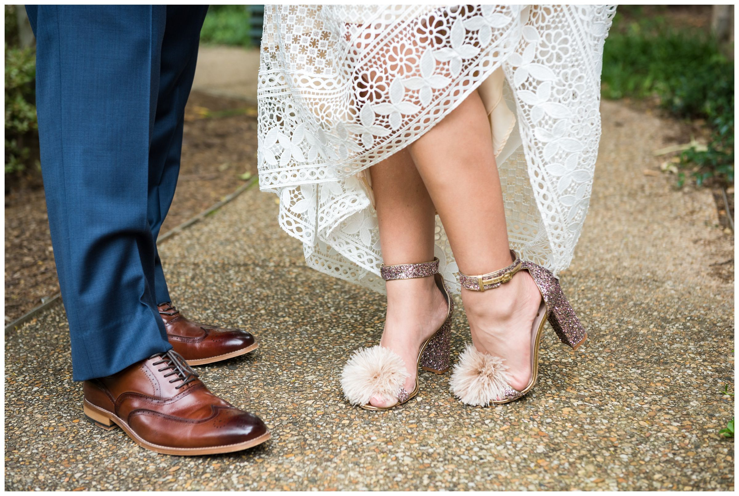 Detail photo of groom's navy Hilfiger suit and brown shoes and bride's BHLDN wedding dress and sparkly pom Kate Spade pink shoes