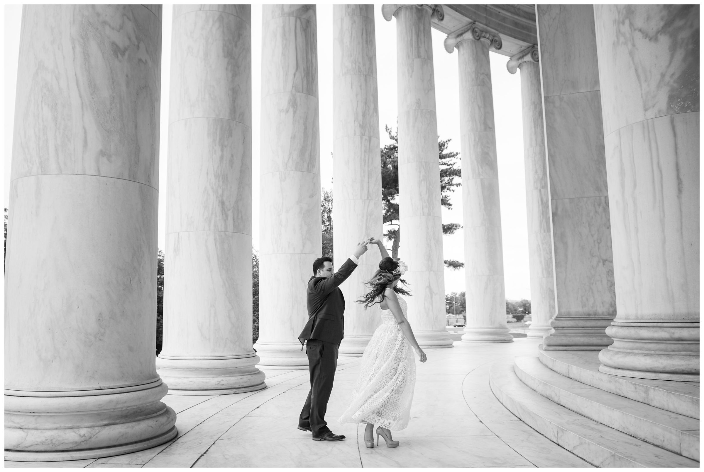 groom twirling bride amongst columns at the Jefferson Memorial during DC monument wedding day in Washington