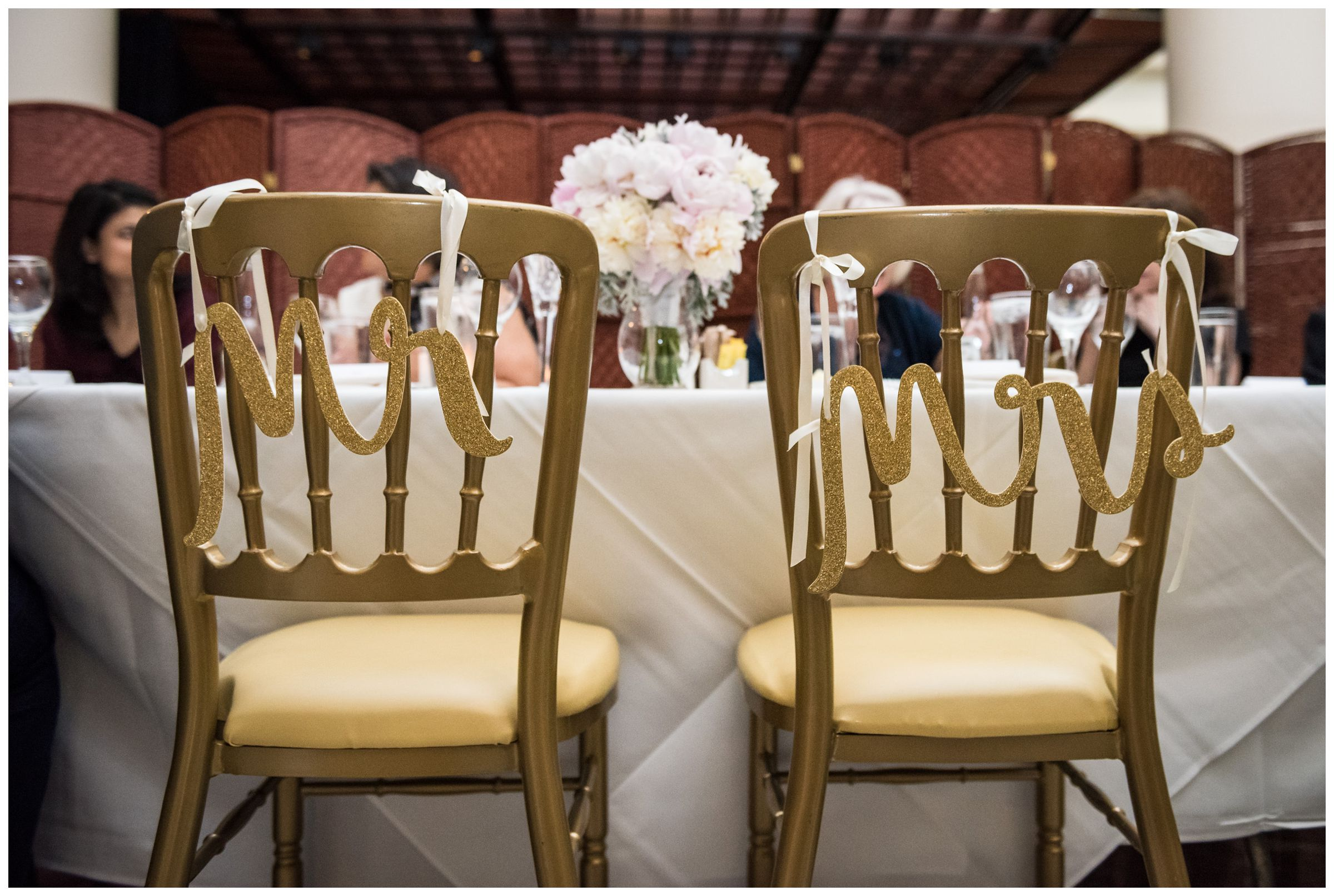 Mr. and Mrs. signs on bride and groom's chairs during intimate wedding reception dinner at Old Ebbitt Grill in Washington, D.C.