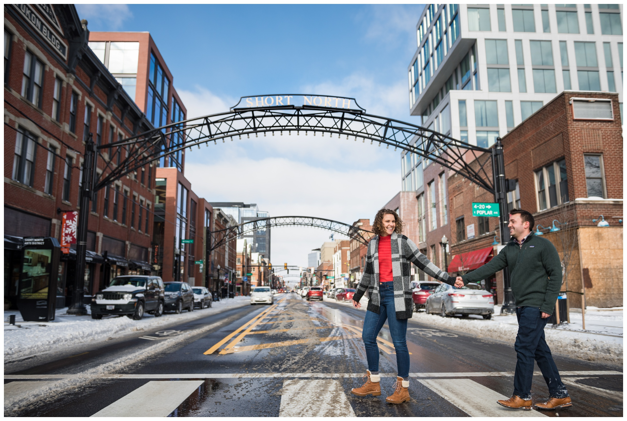 engaged couple walking under arches in the Short North neighborhood of Columbus, Ohio during snowy winter engagement session