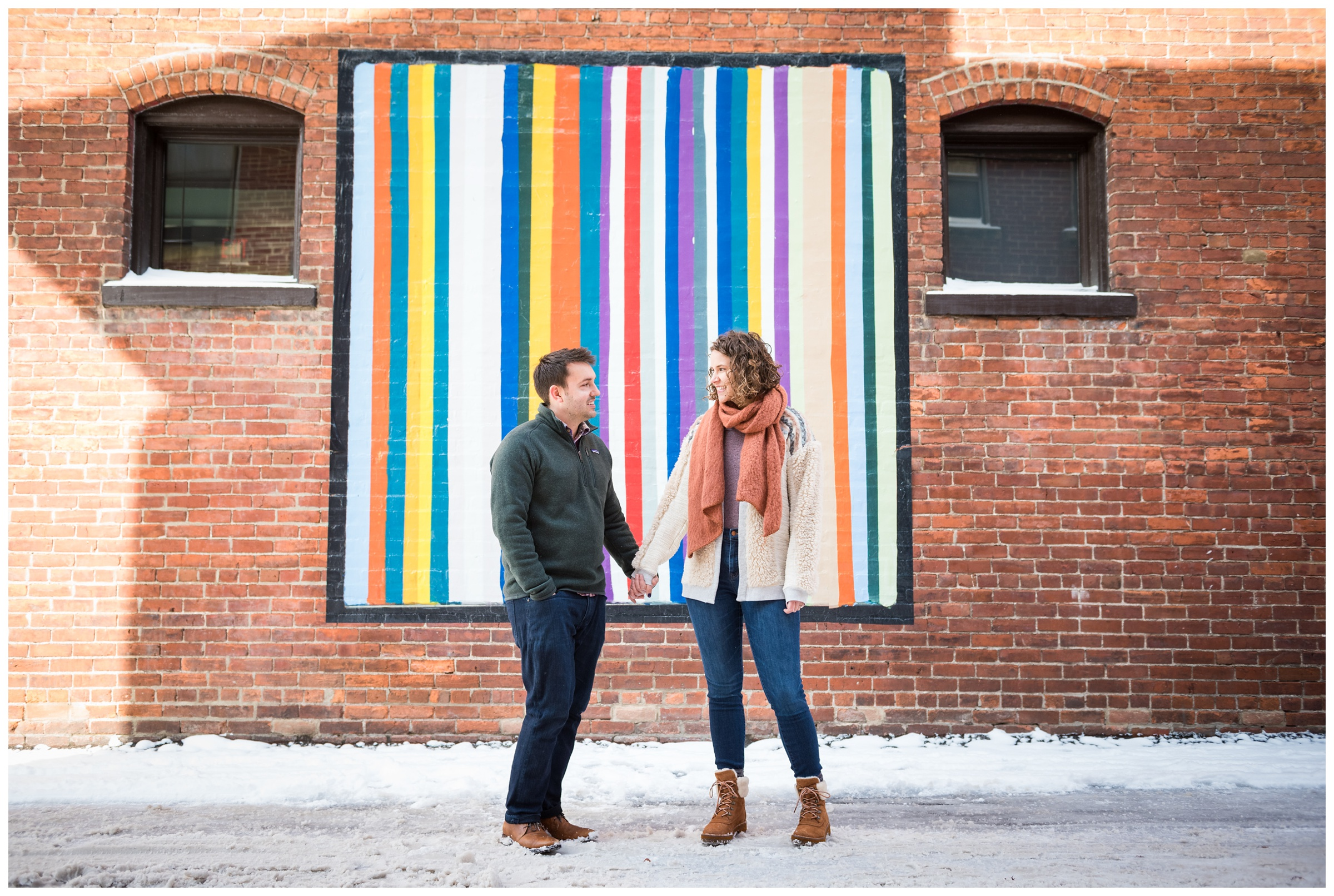 winter engagement photos in front of brick wall and mural in the Short North area of Columbus, Ohio