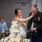 bride smashing cake into groom's face after Marine military sword cake cutting
