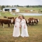 two brides kissing on farm with cows by LGBTQ friendly columbus wedding photographer