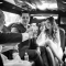 wedding party cheers in limo on the way to reception