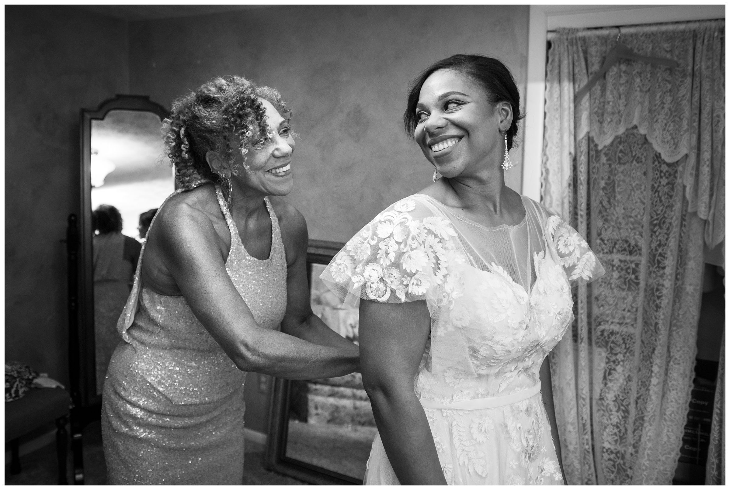 African American mom helping bride daughter into gown before Columbus Ohio wedding at Jorgensen Farms Historic Barn