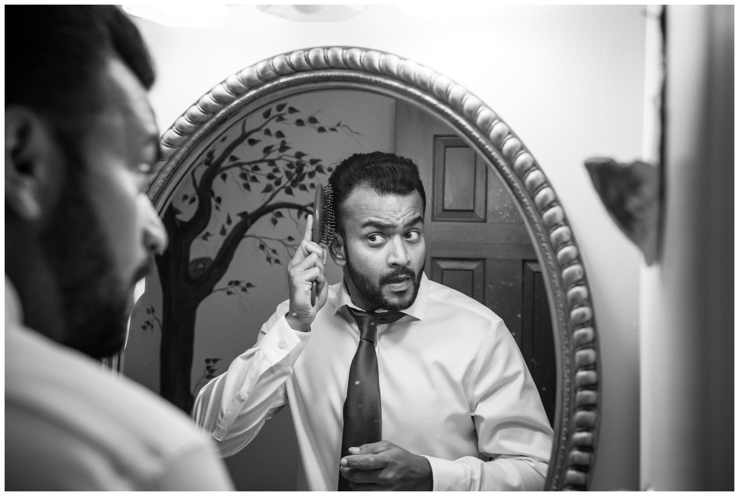 Indian wedding groom getting ready and combing hair in mirror