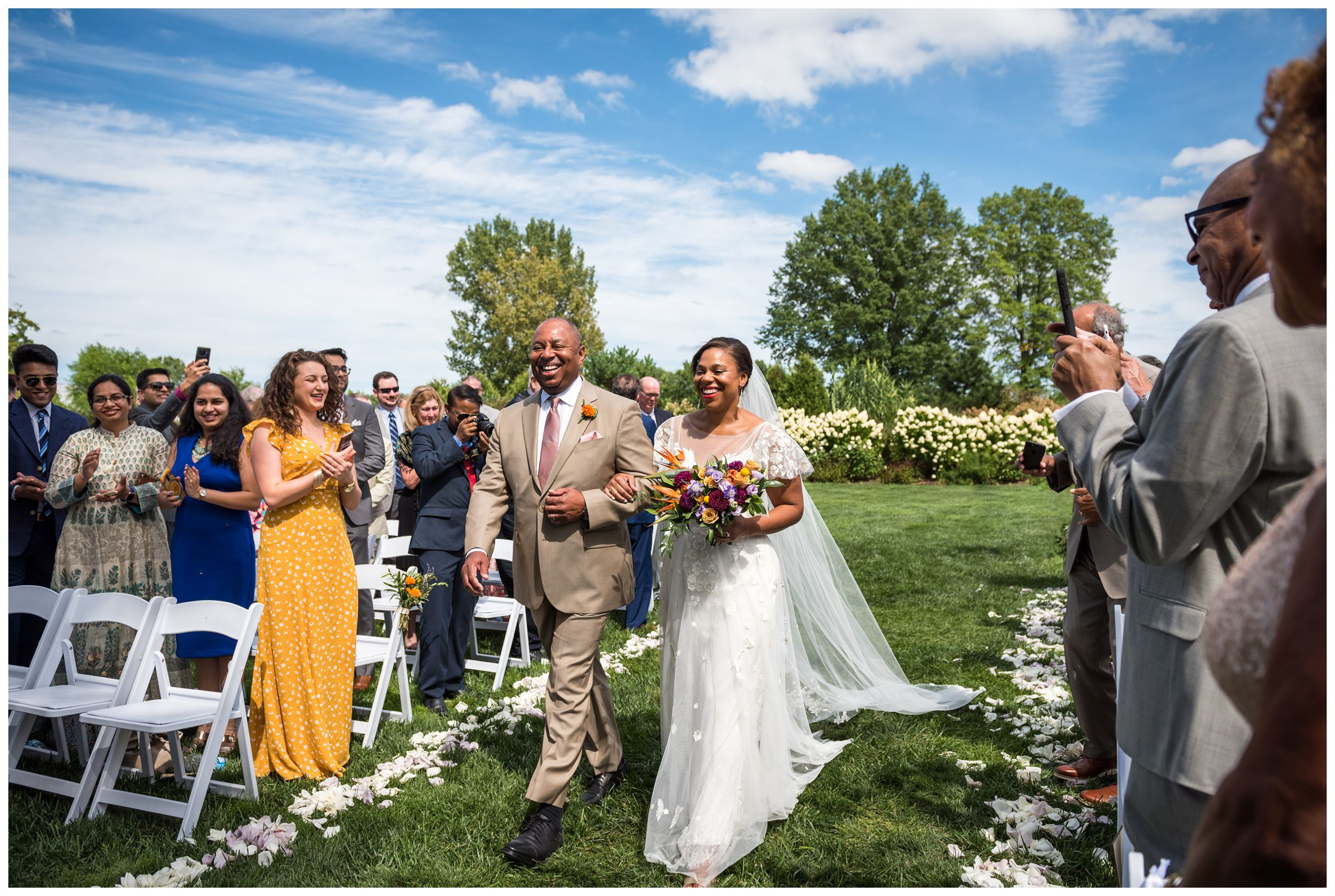 African American bride walking down aisle with father during summer Jorgensen Farms wedding