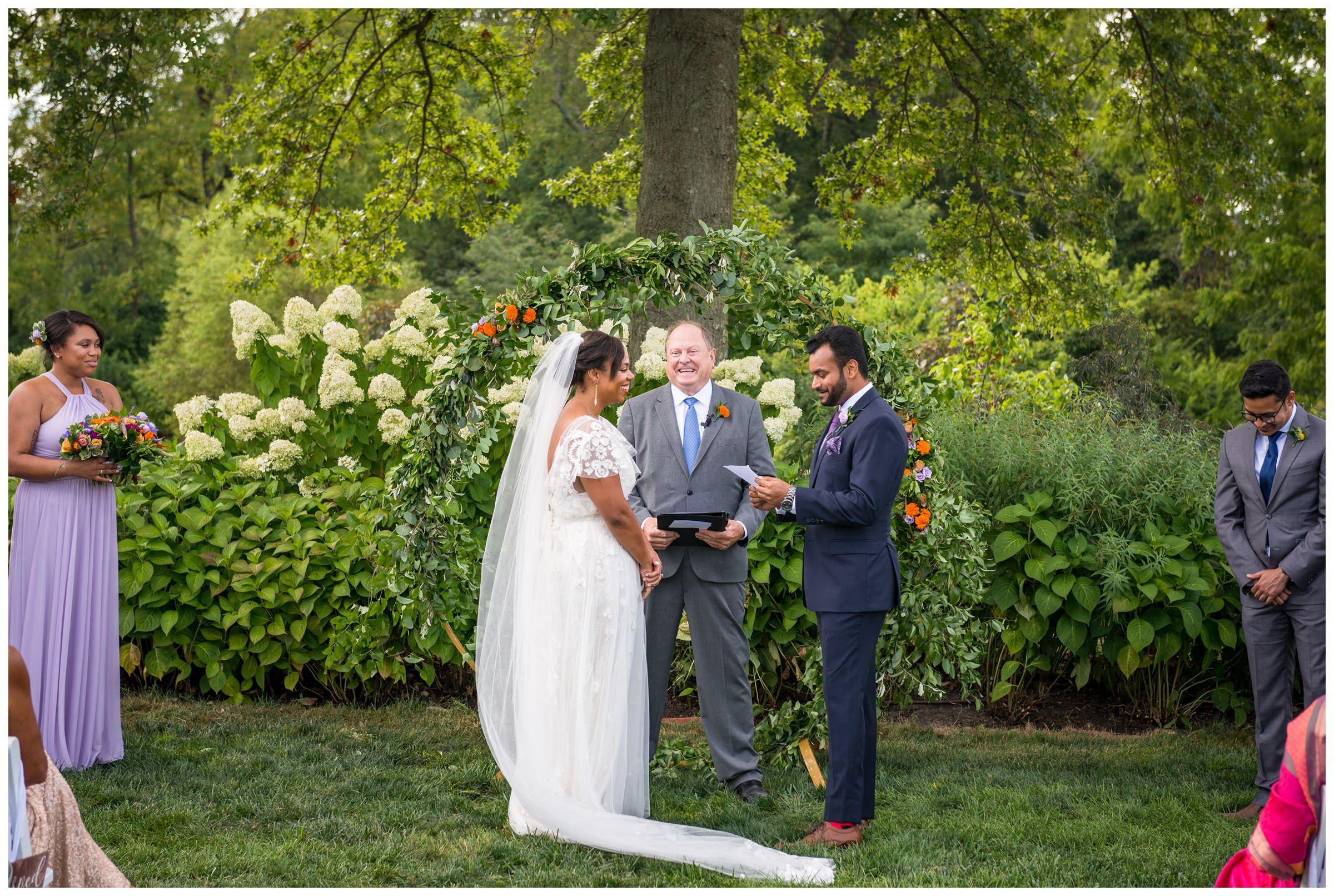 groom reading vows during wedding ceremony in front of floral moongate arch at Jorgensen Farms flower field