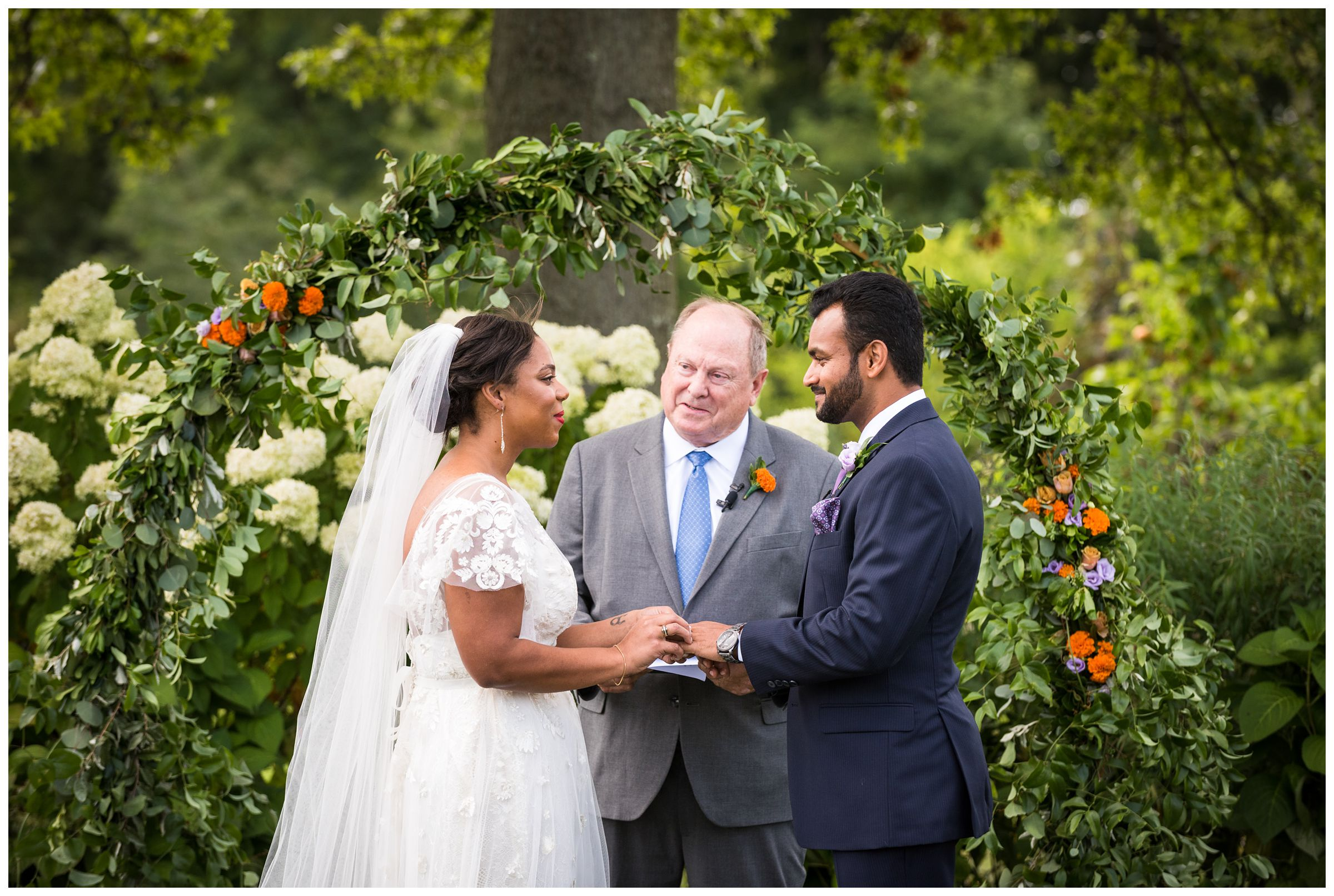 bride an groom exchange ring during summer wedding in front of floral arch with marigolds at Jorgensen Farms