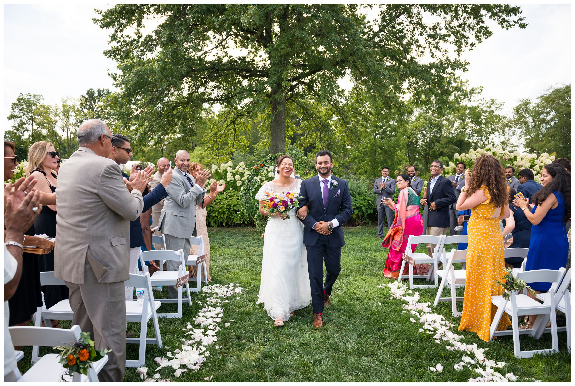 bride and groom exit wedding ceremony after colorful summer Indian wedding at Jorgensen Farms