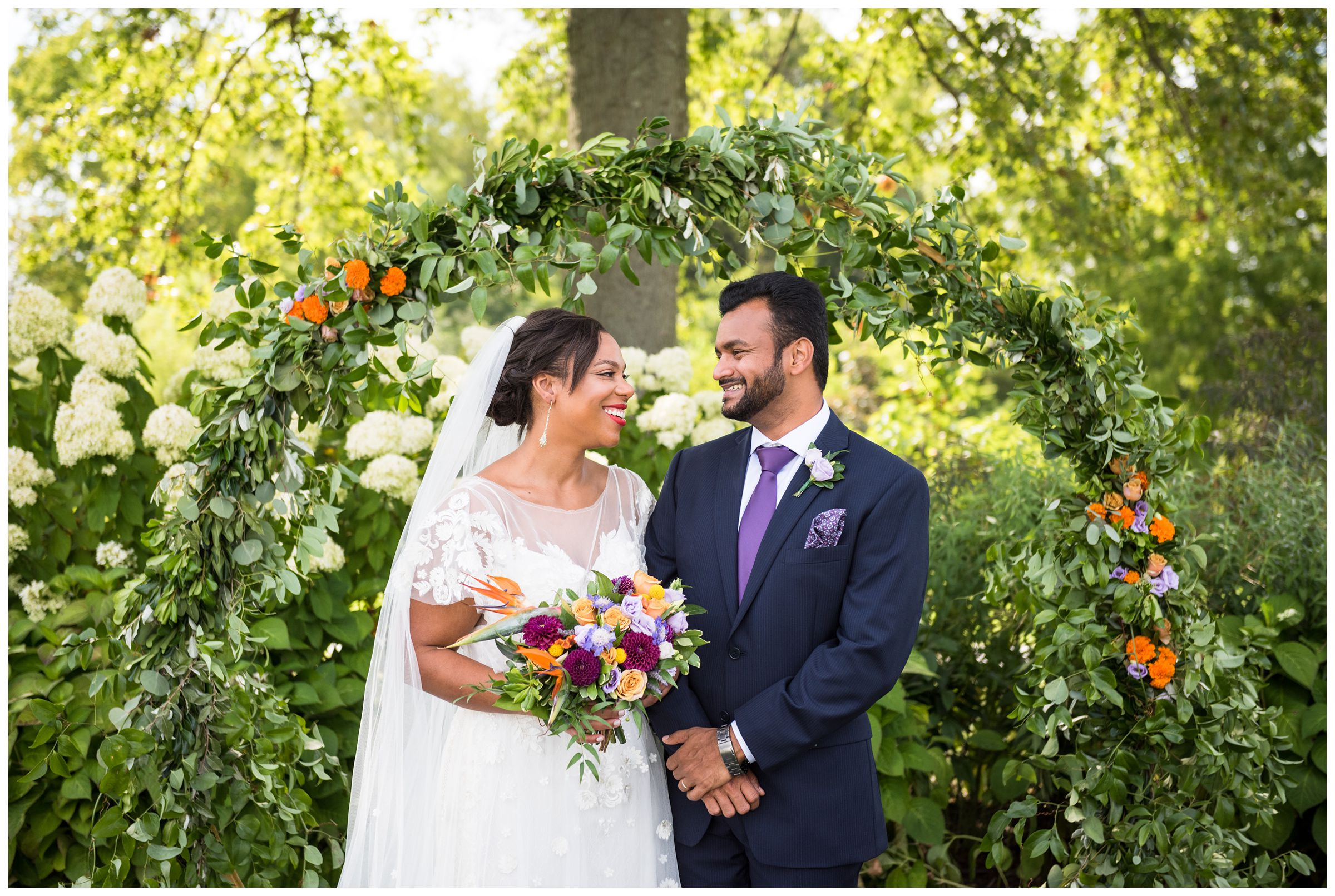 Columbus wedding photography of black bride and Indian groom under floral moongate arch with colorful purple and orange flowers