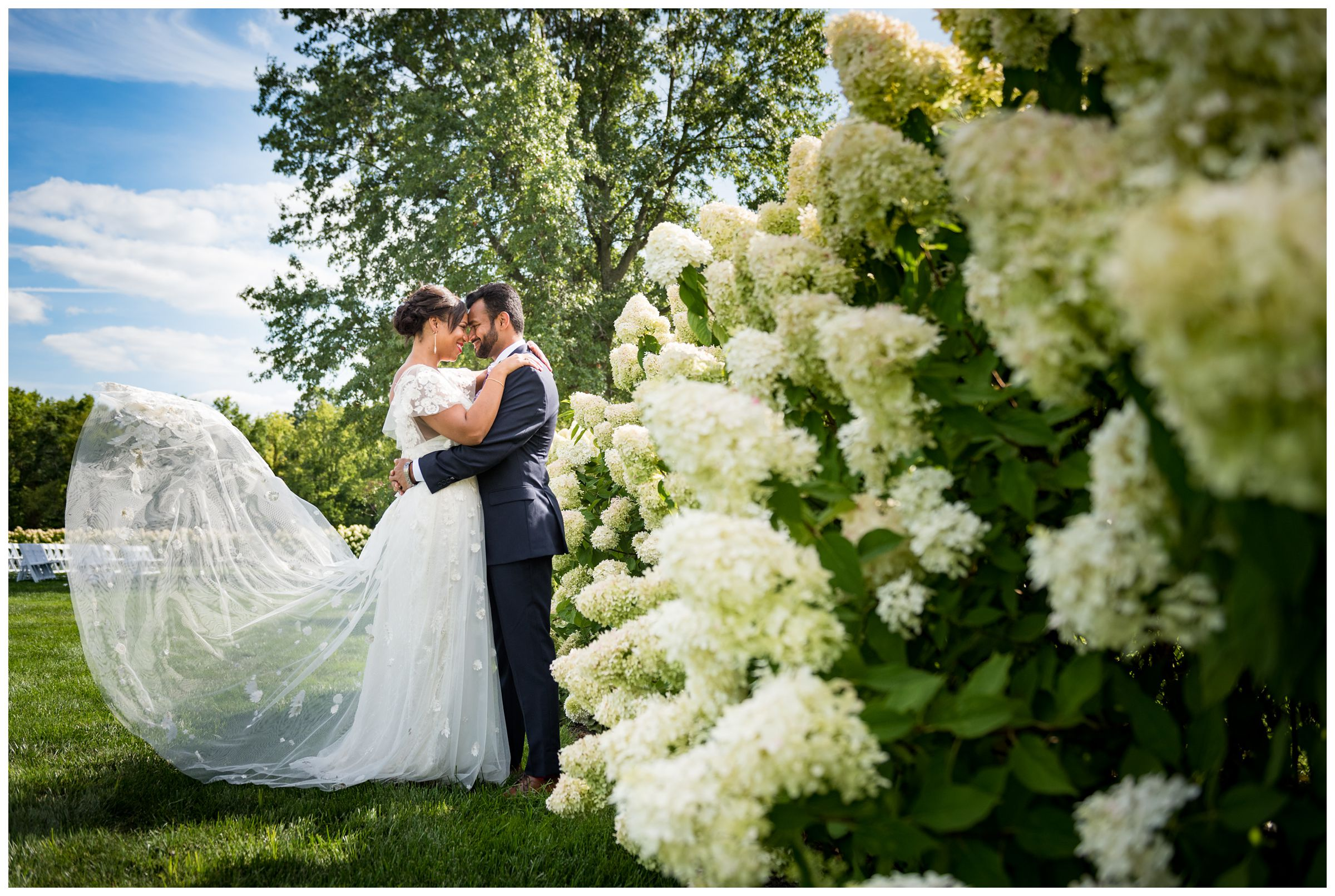 groom and bride with flowy lace wedding dress portrait with hydrangeas at Jorgensen Farms