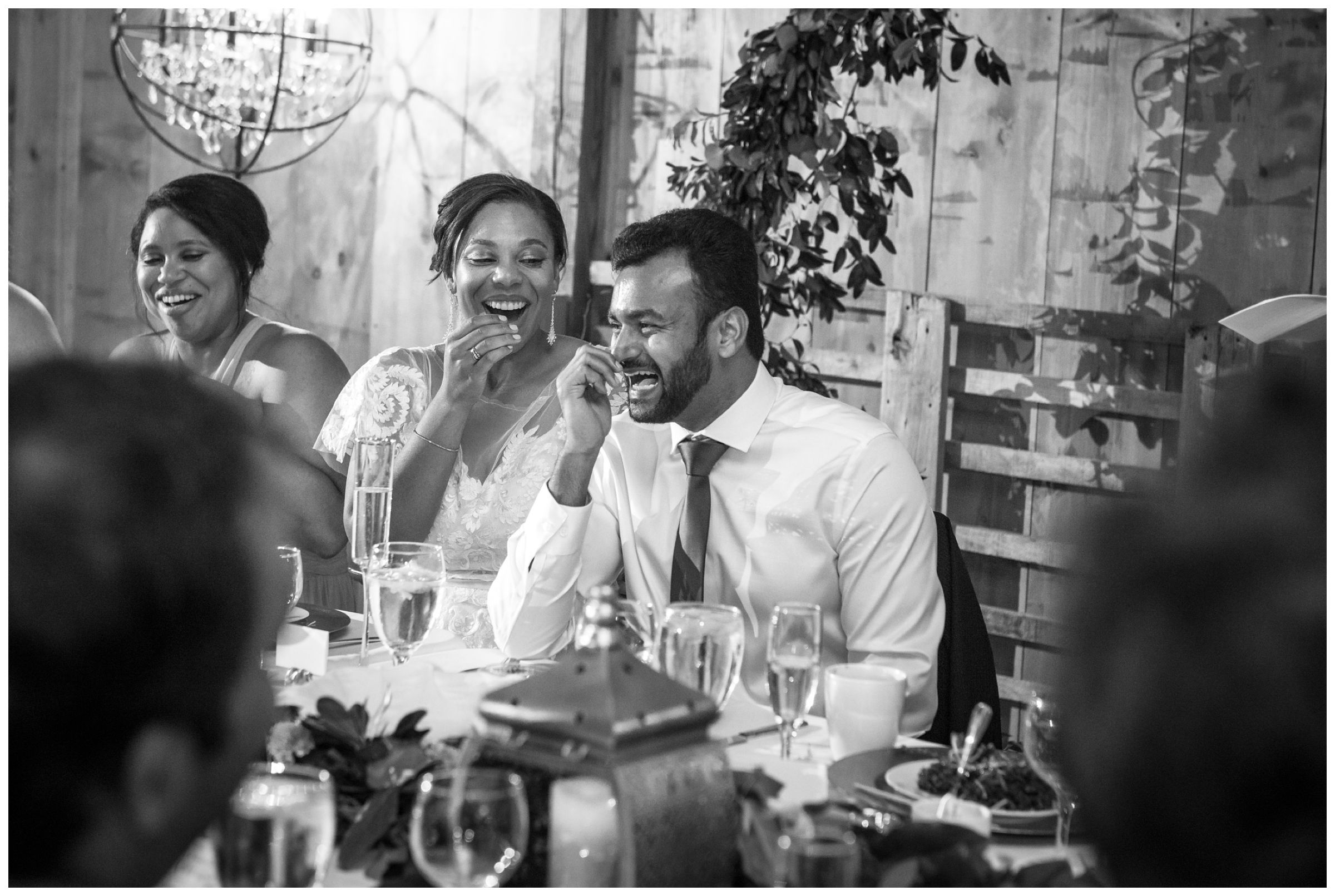 bride and groom laughing at wedding toast during barn wedding reception in Columbus