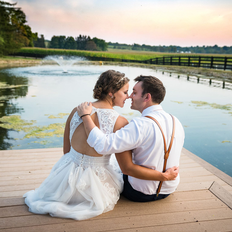 bride and groom sitting on a dock by a pond at sunset during a barn wedding reception on their family farm in Lancaster Ohio