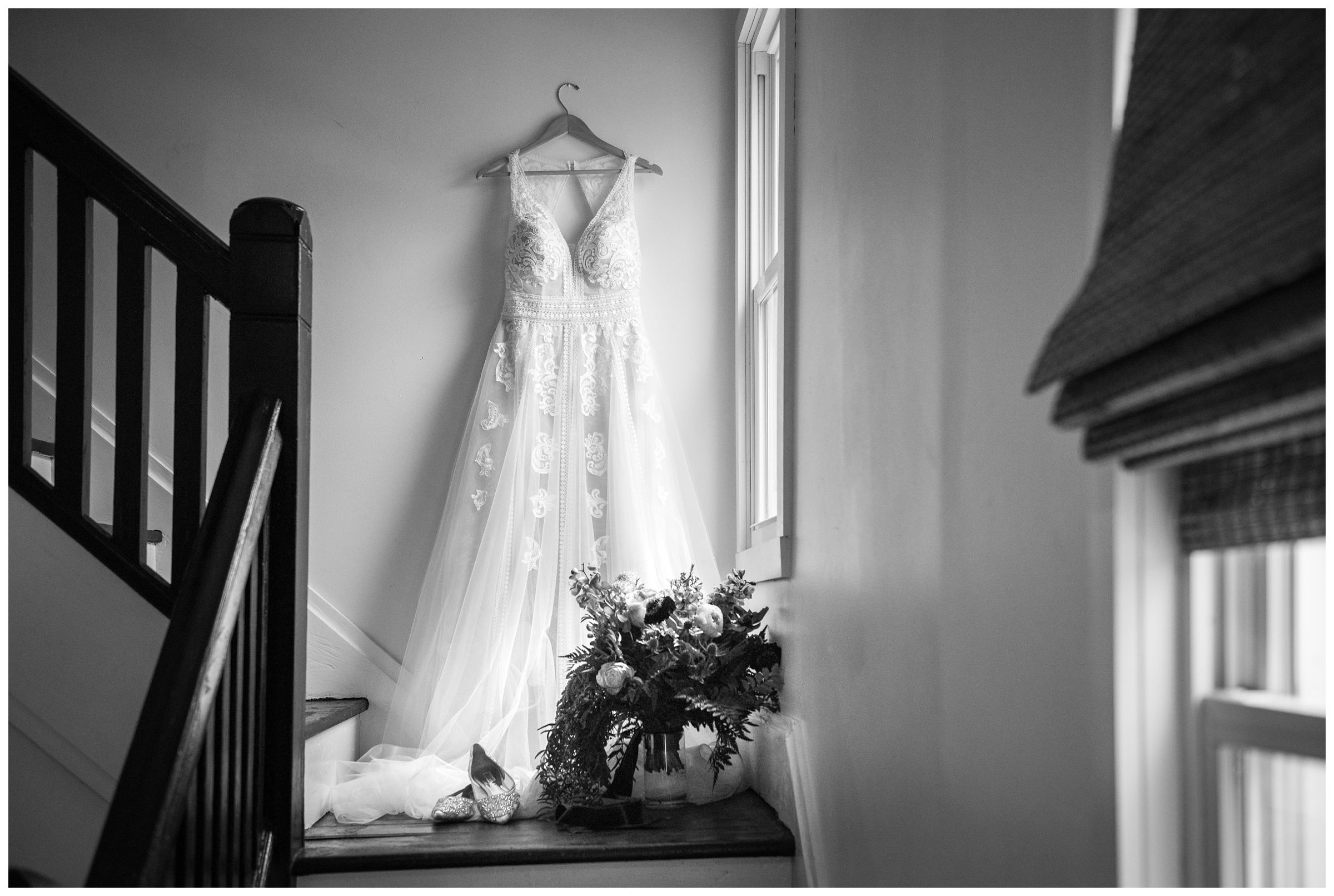 lace a-line wedding dress hanging on stairway by window with bouquet and shoes