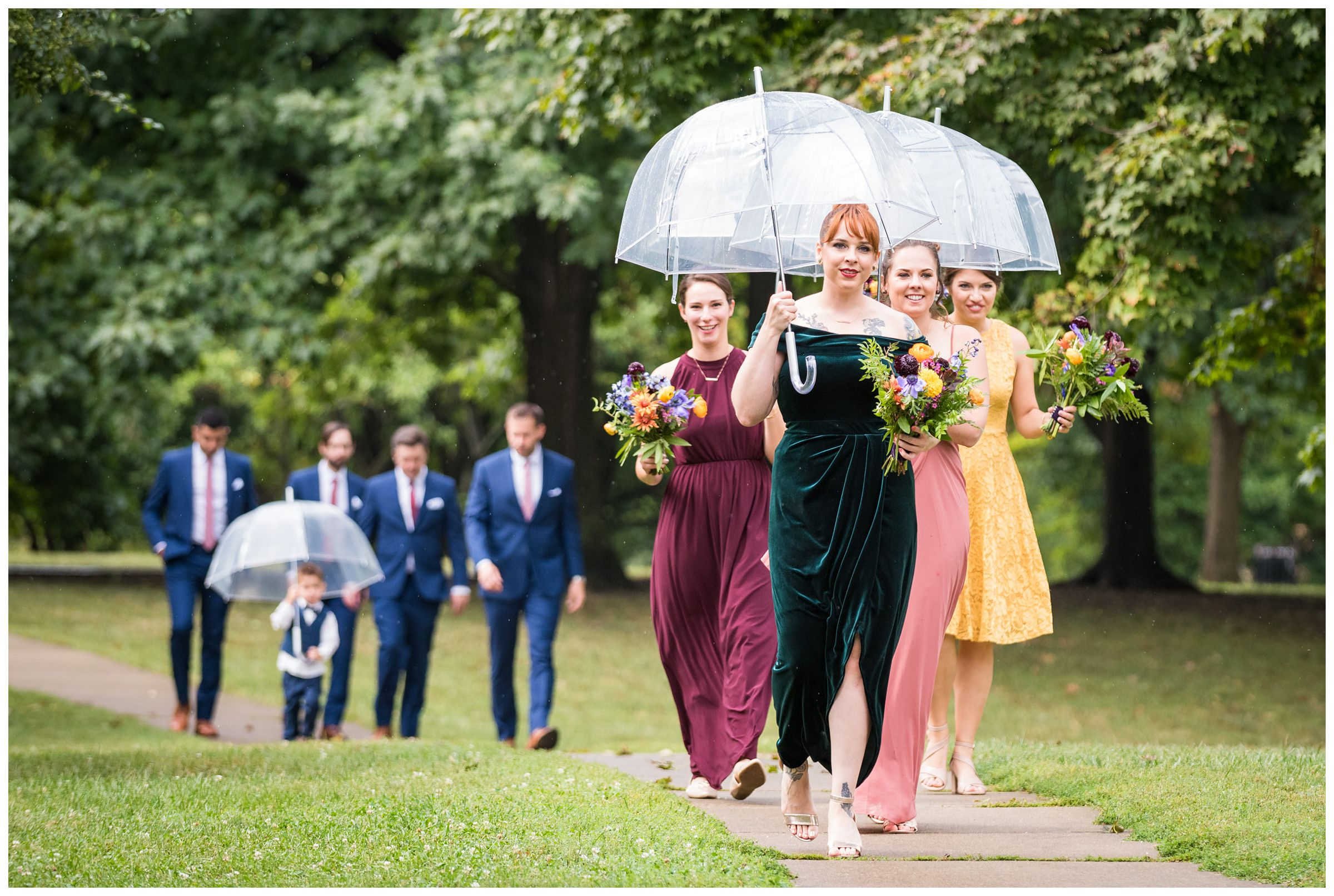 bridesmaids carrying umbrellas during a rainy wedding day in Goodale Park in Columbus