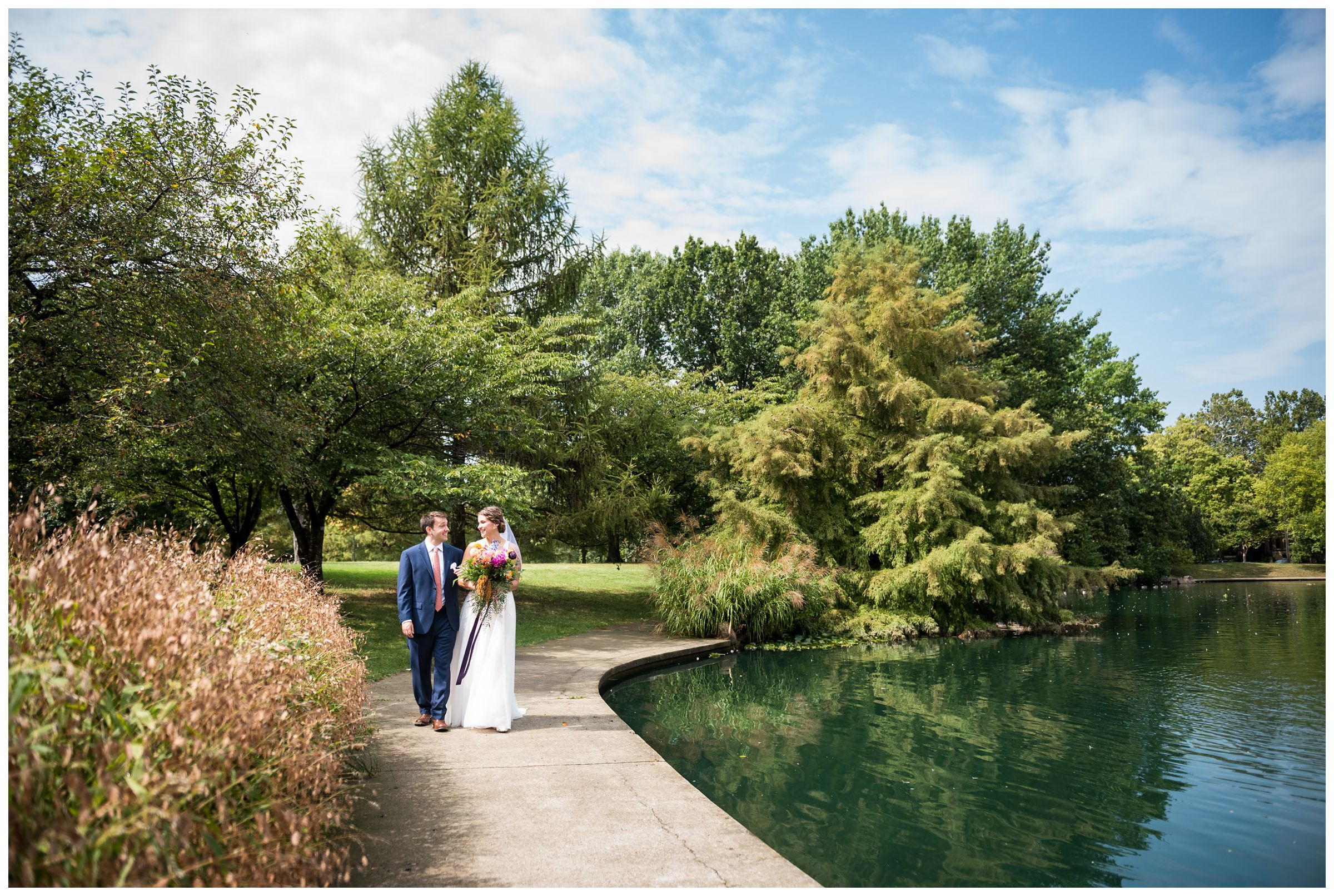 bride and groom walking along pond at Goodale Park in before wedding in Columbus, Ohio