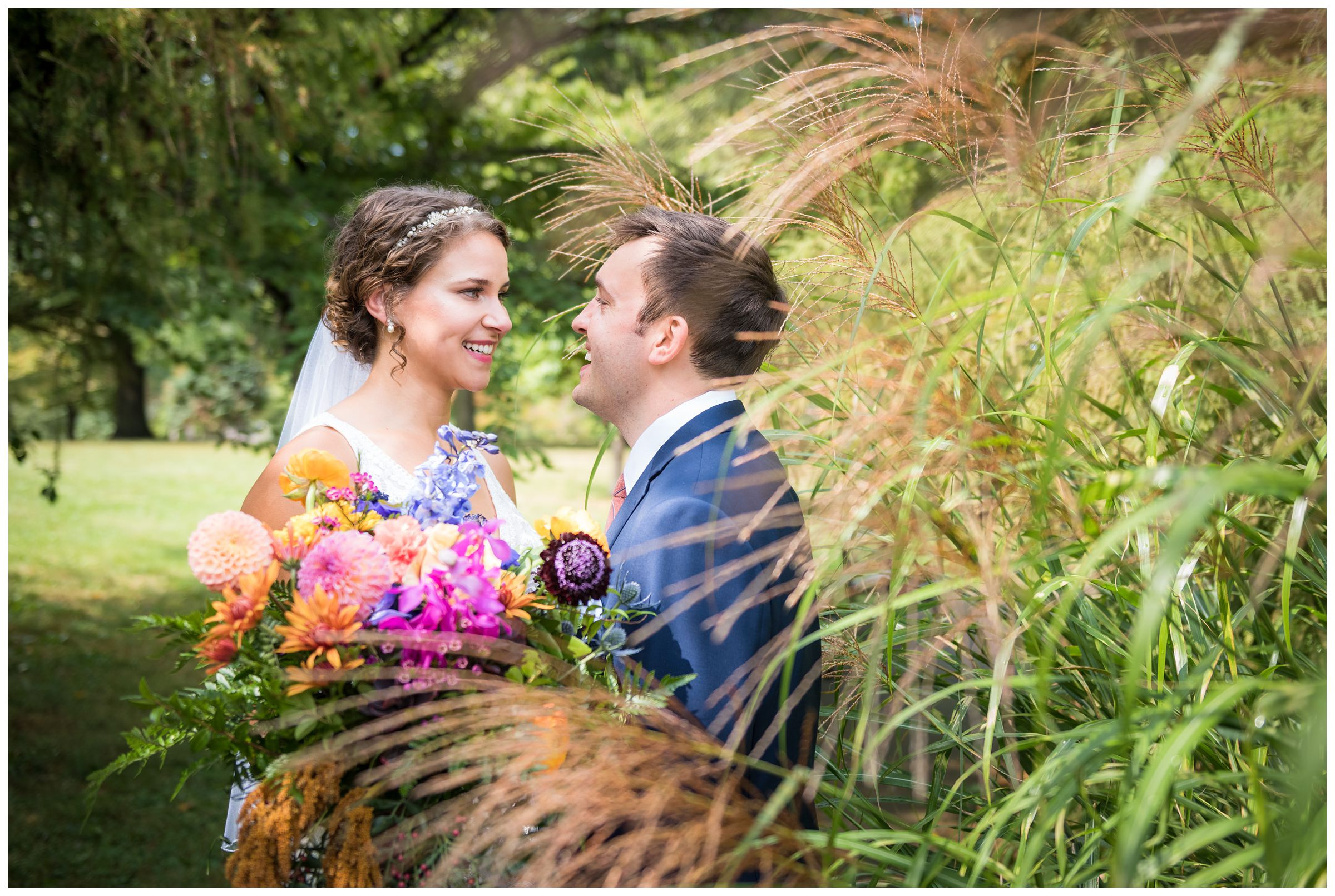 bride and groom among the tall grass at Goodale Park during wedding photos in Columbus Ohio