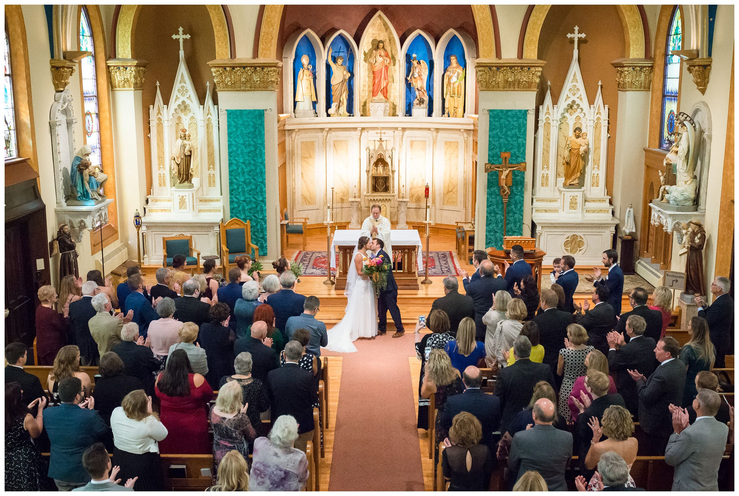 first kiss from balcony during indoor wedding ceremony at St. John the Baptist Catholic Church in the Short North in Columbus, Ohio