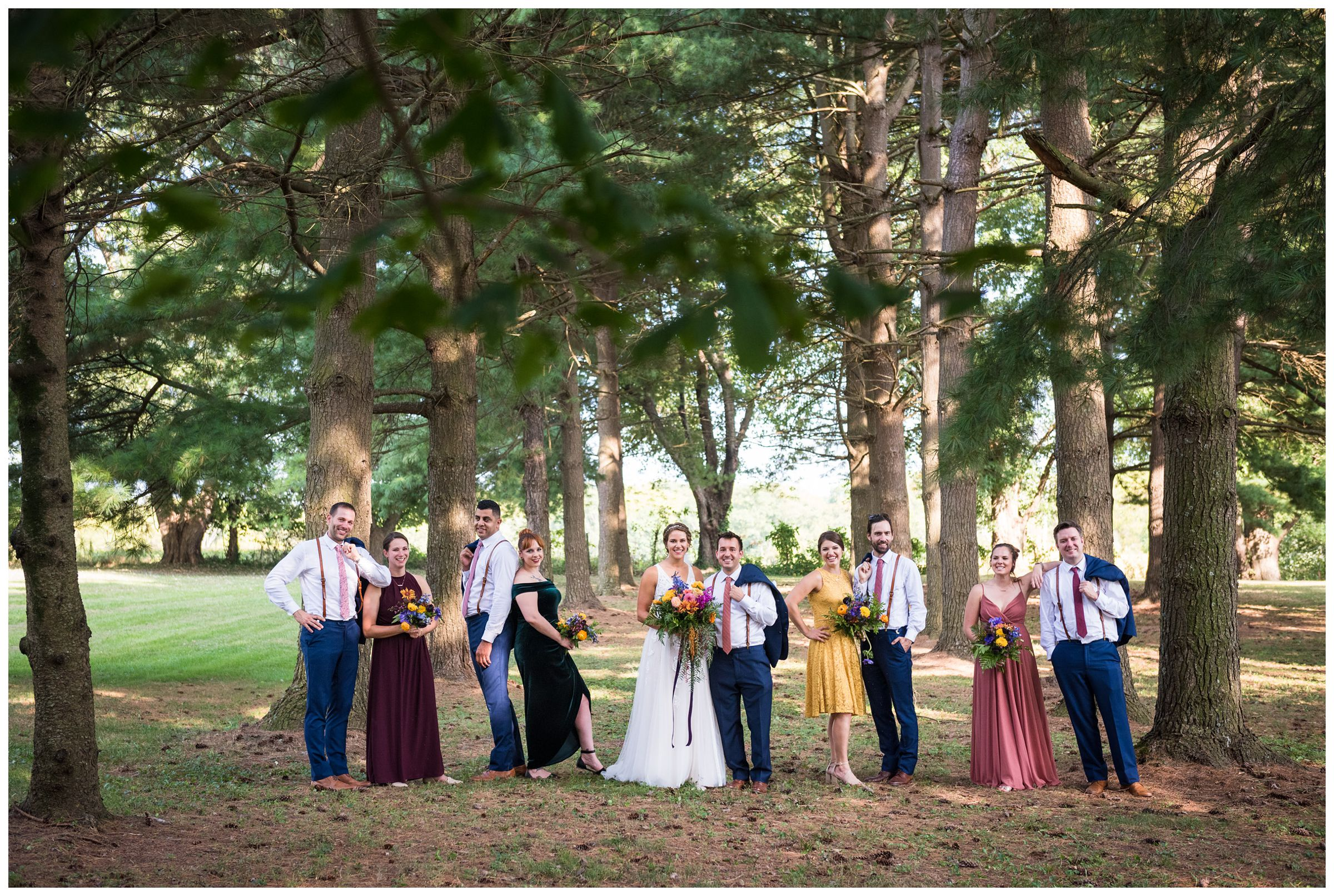 wedding party in fall colors under pine tree forest during rustic barn wedding in Lancaster, Ohio