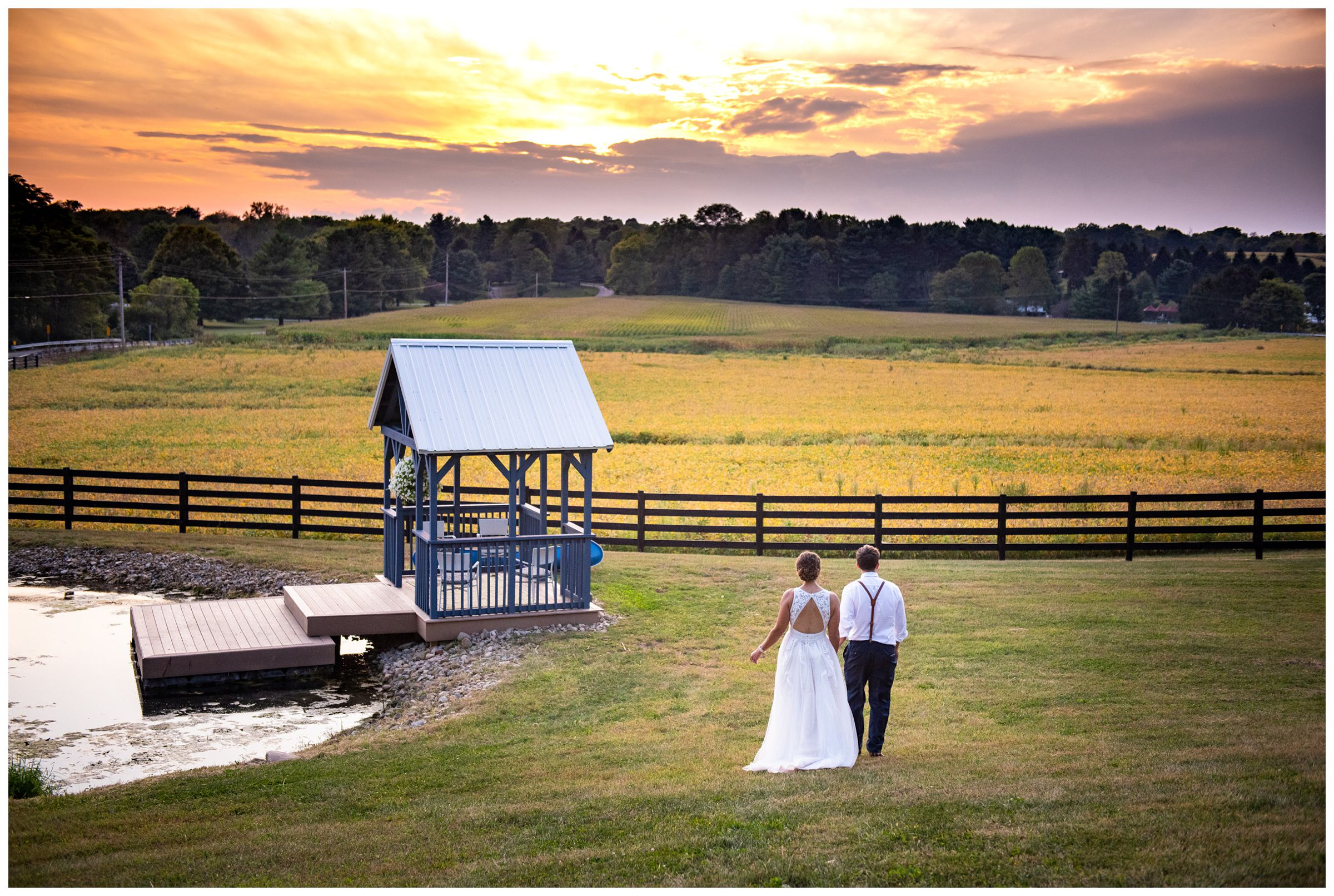 bride and groom walking at sunset by pond during rustic farm wedding captured by Columbus Ohio wedding photographer