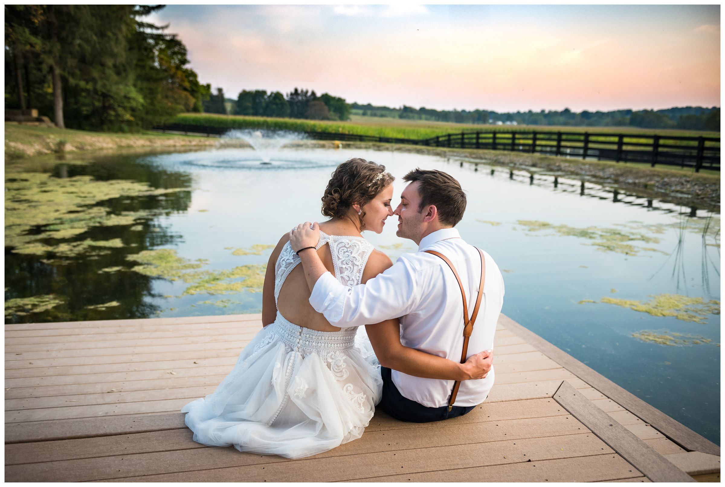 bride and groom sitting on dock by pond at sunset during rustic Lancaster barn wedding captured by Ohio wedding photographer