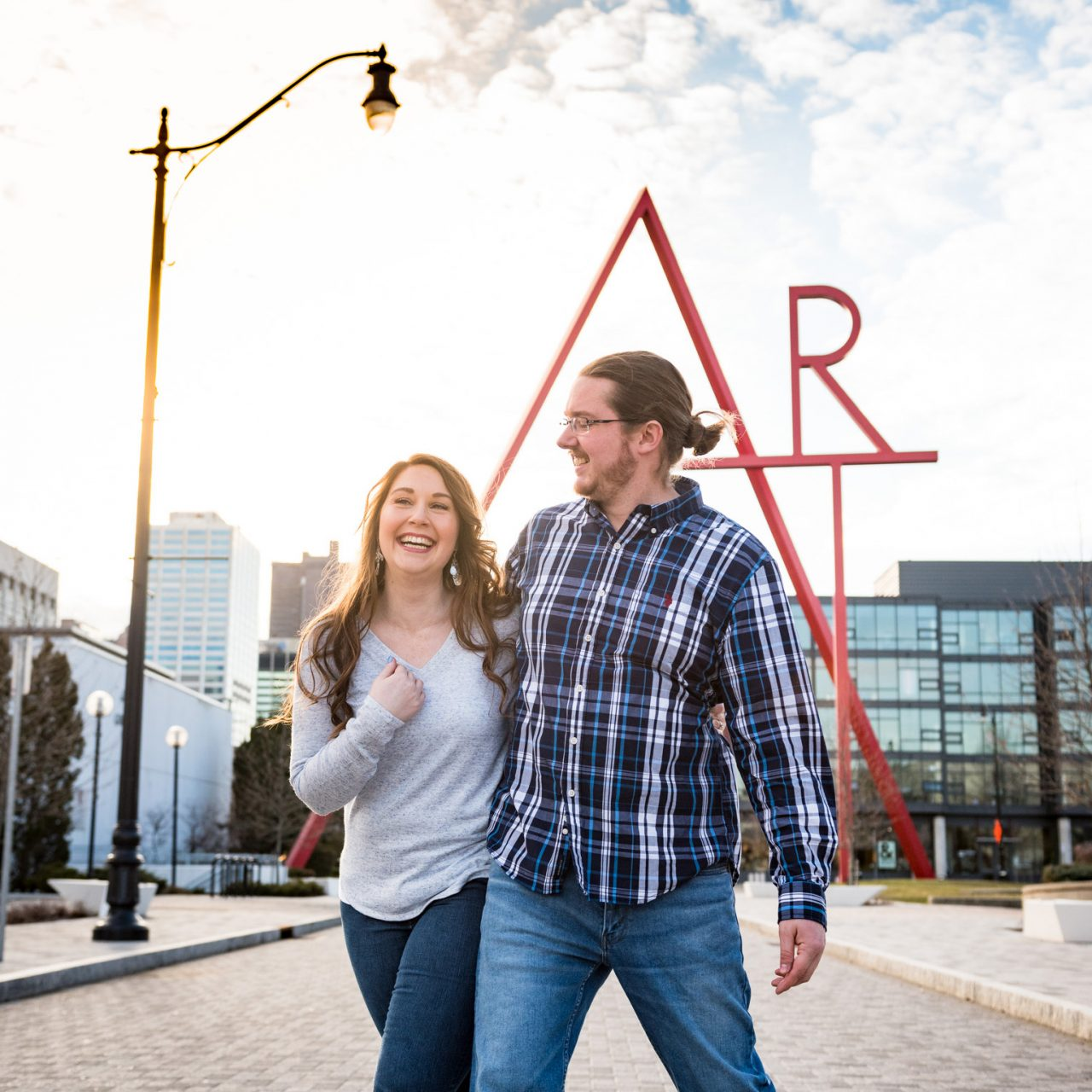 Engaged couple laughing outside the Columbus Museum of Art with an ART sculpture in the background.