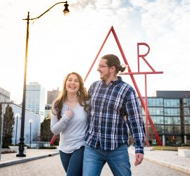 engaged couple laughing in front of Art sculpture in downtown Columbus