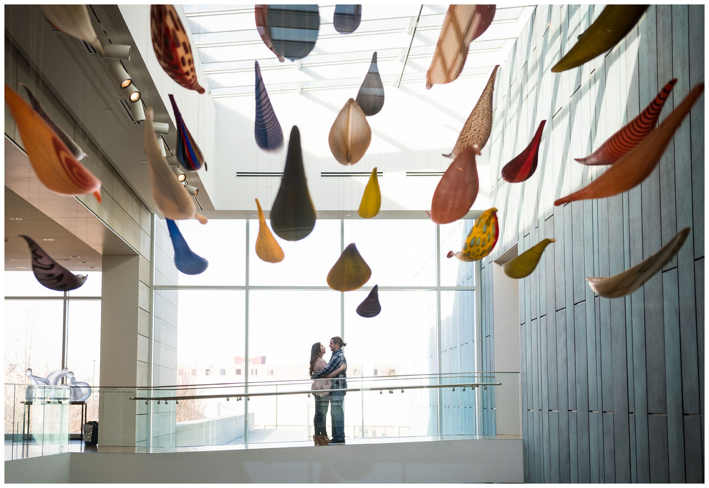 Engaged couple standing in the atrium of the Columbus Museum of Art surrounded by colorful hanging glass artwork.