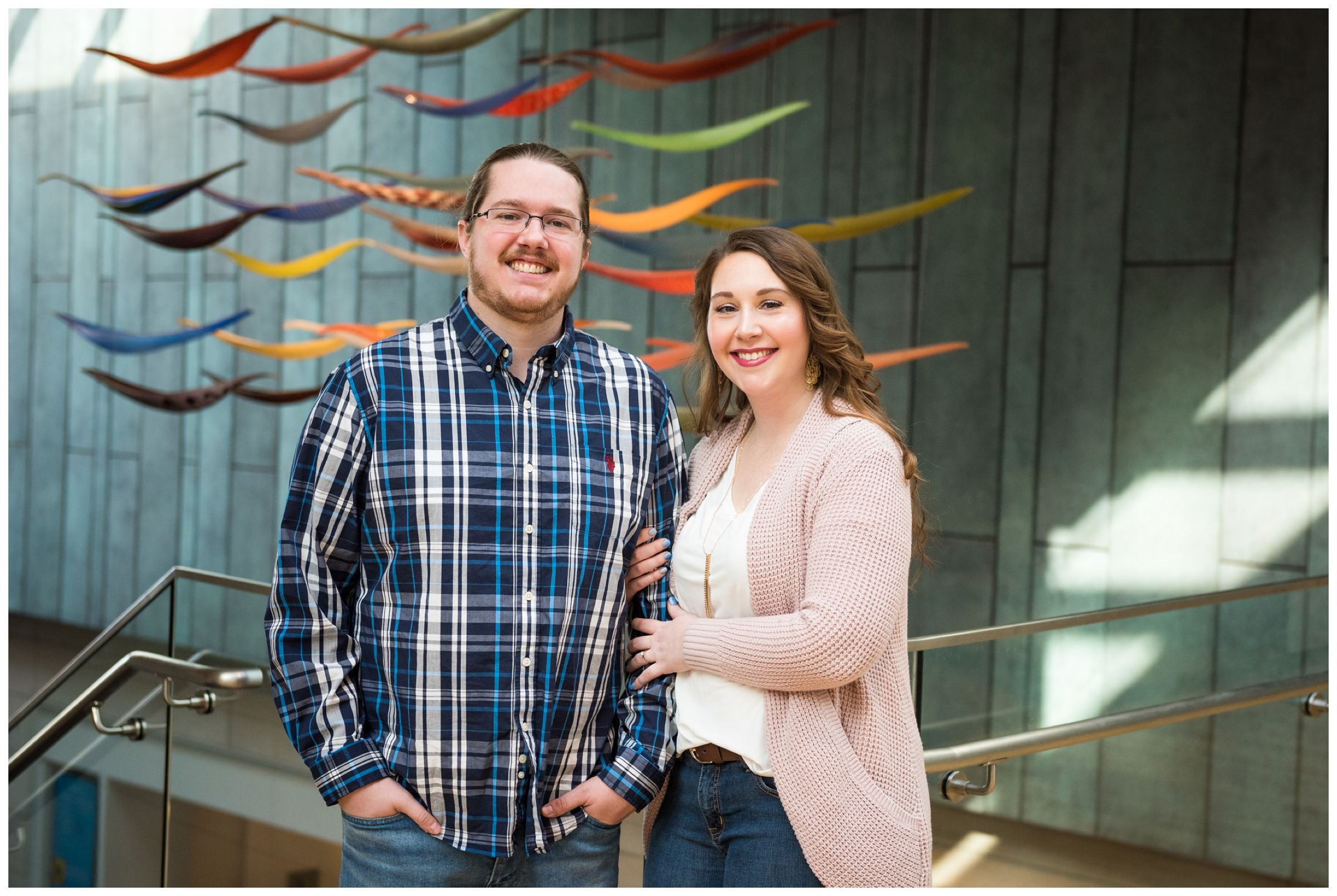 Winter indoor engagement photos in the atrium of the Columbus Museum of Art surrounded by colorful hanging glass artwork.