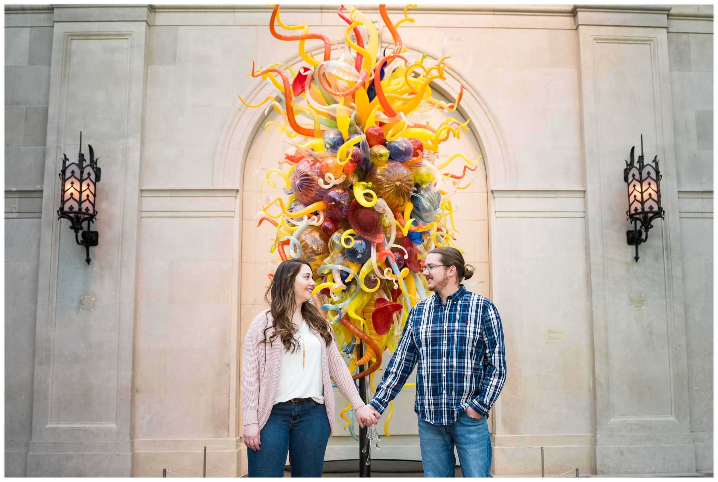 Engaged couple holding hands in front of a Chihuly glass sculpture at the Columbus Museum of Art in Ohio
