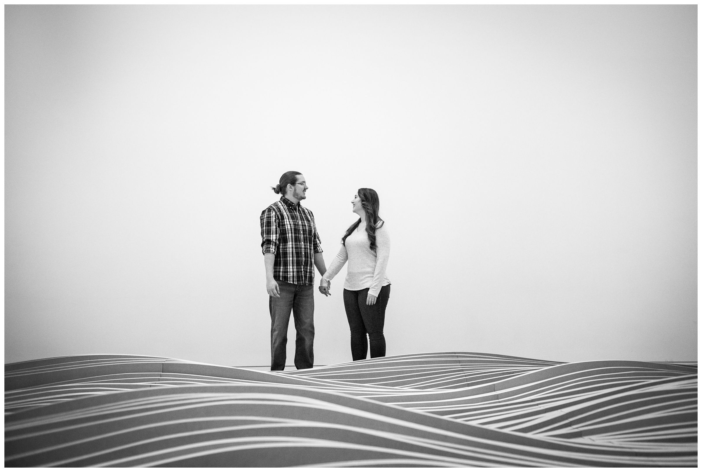 engaged couple standing behind wavy wood sculpture at the Columbus Museum of Art