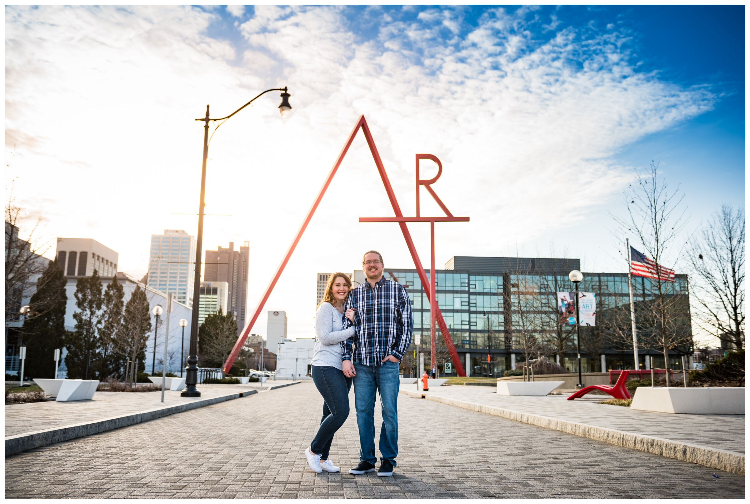 engaged couple photographed in front of Art sculpture in downtown Columbus by Ohio wedding photographer