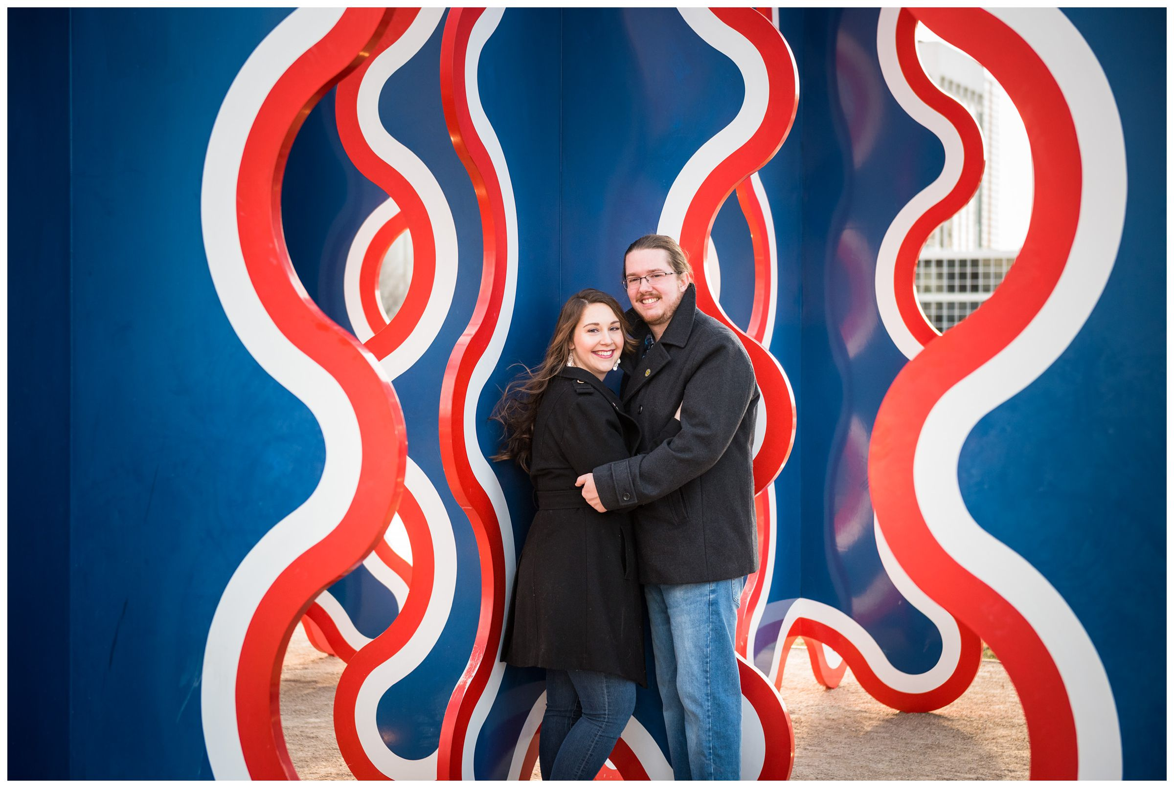 couple in front of blue and orange sculpture